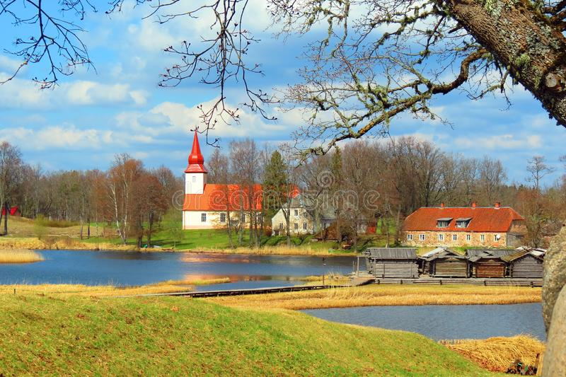 Igreja, casa e lago, Letónia fotografia de stock royalty free