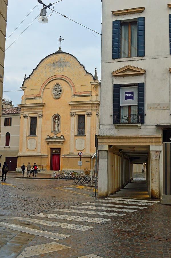 Igreja colorida de creme ao lado das lojas dianteiras com arcadas na rua de compra imagens de stock