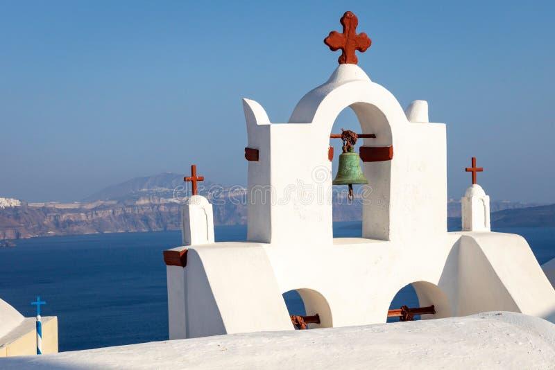 Igreja com cruz vermelha na ilha de Thirasia que negligencia Oia e Thira em Santorini, Grécia fotos de stock