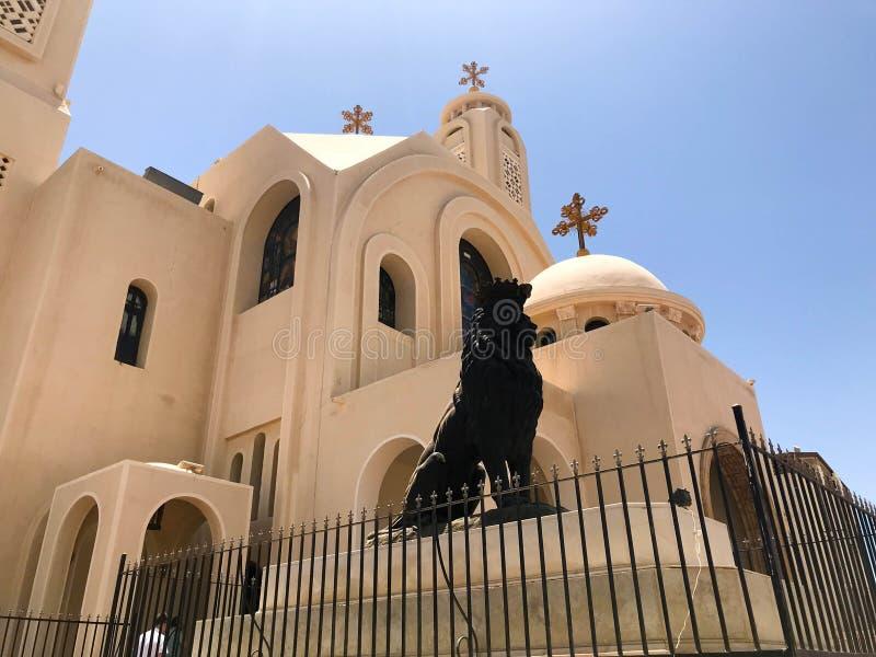 A igreja cristã ortodoxo de pedra branca bege bonita velha é um lugar para rezar ao deus com uma cruz e a uma estátua de um l pre foto de stock
