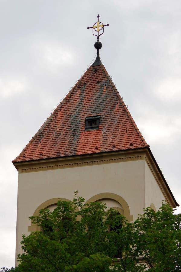Igreja da vila em Baden Wuerttemberg, em Pforzheim, em Alemanha, em uma torre e no telhado de ardósia, céu nebuloso fotografia de stock royalty free
