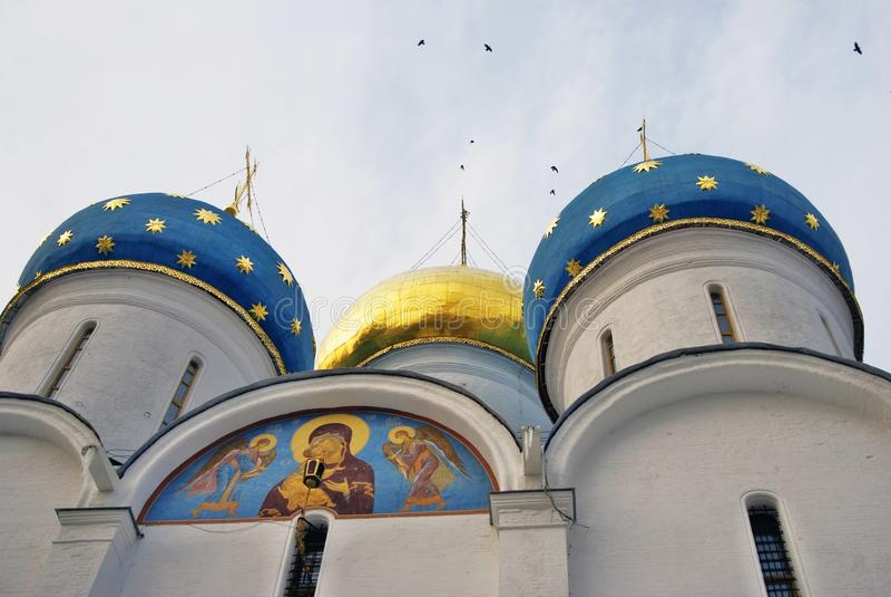 Igreja de Dormition da trindade Sergius Lavra Os pássaros voam em torno das cúpulas imagens de stock