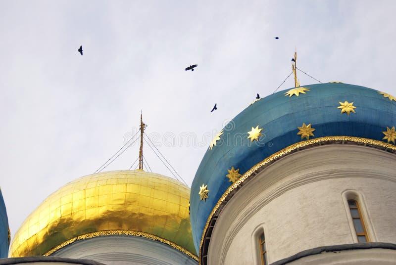 Igreja de Dormition da trindade Sergius Lavra Os pássaros voam em torno das cúpulas fotografia de stock