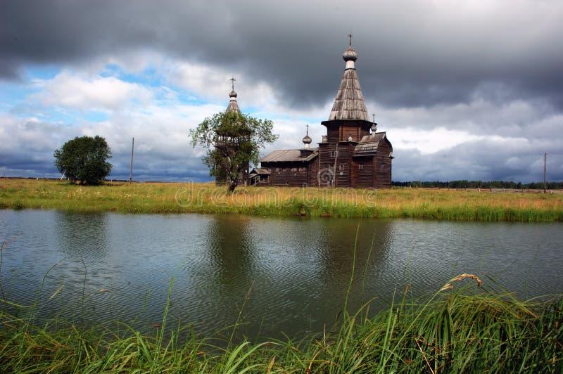 Igreja de madeira antiga além do rio, céu tormentoso foto de stock
