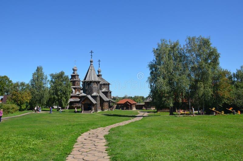 Igreja de madeira velha e outras construções no museu da arquitetura de madeira em um dia de verão ensolarado na cidade de Suzdal imagens de stock