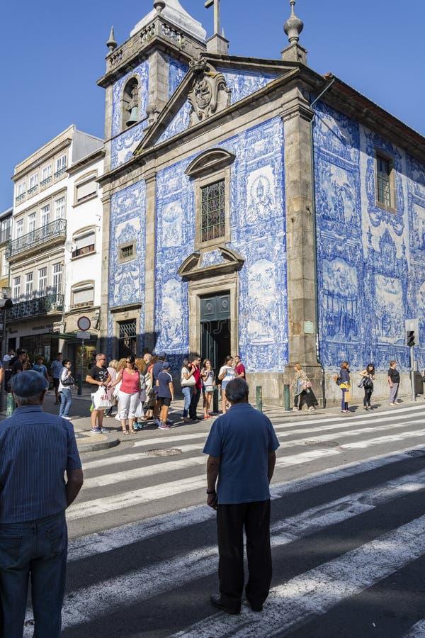 Igreja de Santa Catarina, Porto, Portugal. Homem atravessando a estrada imagem de stock