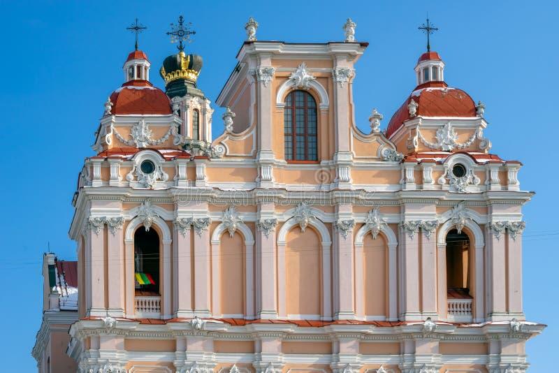 Igreja de St Casimiro em Vilnius e a bandeira de Lituânia no arco foto de stock