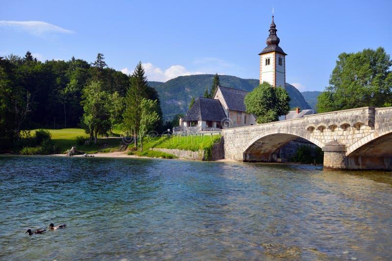 Igreja de St John e ponte velhas da pedra no lago Bohinj, Eslovênia imagem de stock