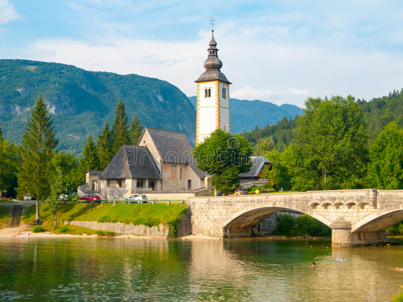 Igreja de St John o batista e a ponte de pedra velha no lago Bohinj na vila alpina Ribicev Laz, Julian Alps, Eslovênia fotos de stock royalty free