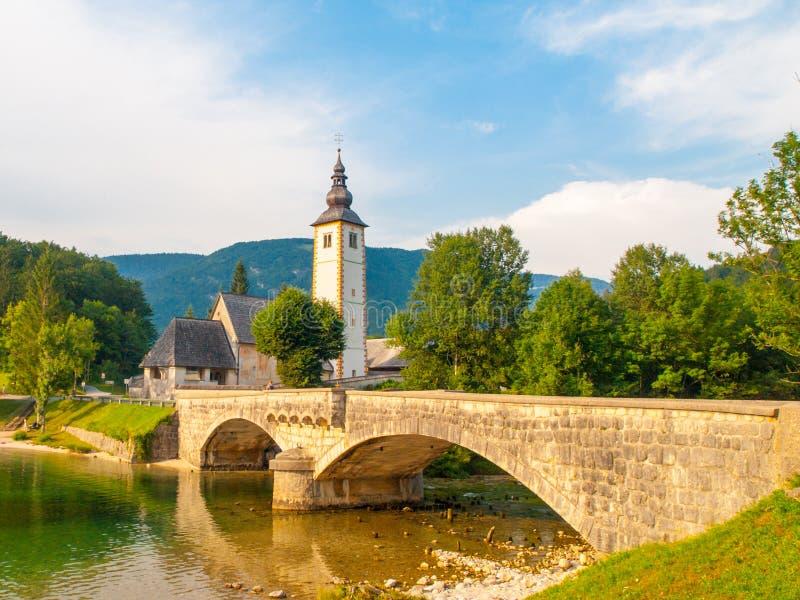 Igreja de St John o batista e a ponte de pedra velha no lago Bohinj na vila alpina Ribicev Laz, Julian Alps, Eslovênia imagem de stock