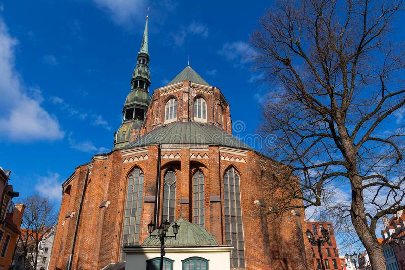 A igreja do ` s de St John e o pináculo da catedral de St Peter, Riga, Letónia fotos de stock