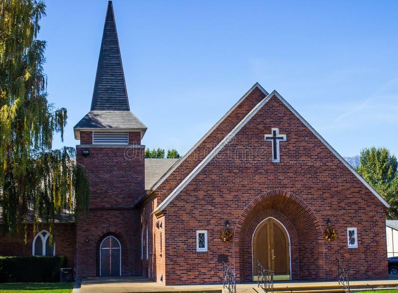 Igreja do tijolo com cruz e torre imagens de stock