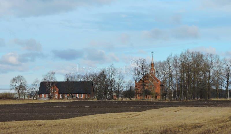 Igreja e casa perto da maneira, Lituânia fotografia de stock royalty free