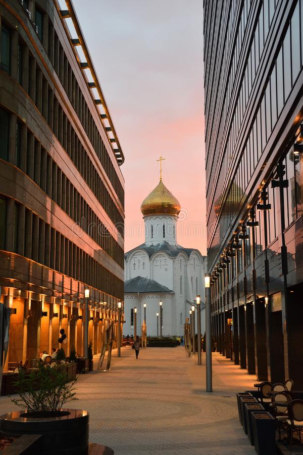 Igreja entre os prédios de escritórios de vidro no por do sol imagem de stock