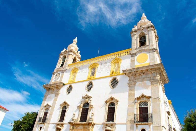 Igreja g?r den Carmo katolska kyrkan i Faro, Algarve Portugal mot bl? byggnadsskywhite royaltyfri fotografi