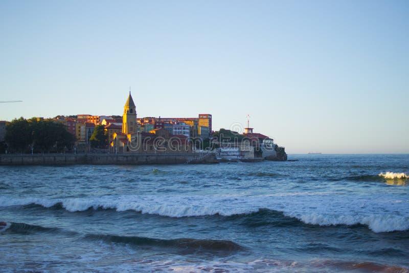 A igreja Iglesia de San Pedro de San Pedro com o mar cant?brico na praia de San Lorenzo, Espanha de Gijon, as Ast?rias fotografia de stock
