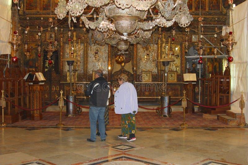 Igreja interior rezando da natividade da Bíblia dos pares idosos, Bethlehem fotografia de stock