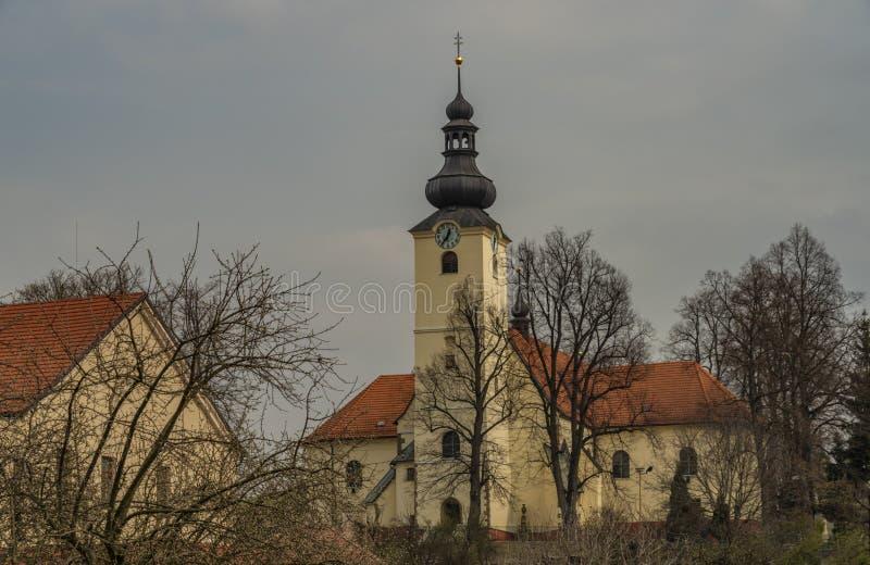 Igreja na cidade de Brumov em Moravia do leste com os telhados vermelhos no dia nebuloso da mola imagens de stock