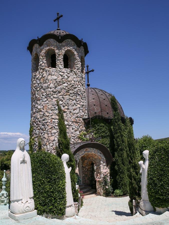 Igreja pequena com esculturas sob o céu agradável foto de stock