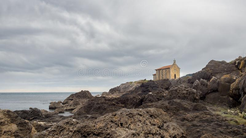 Igreja pequena de Santa Catalina na costa da vila de Mundaca em Biscaia durante um dia nebuloso imagem de stock royalty free