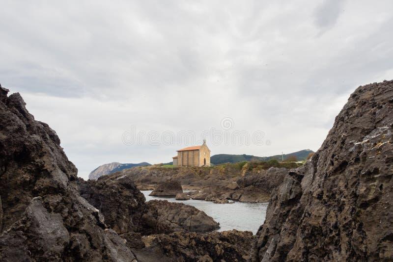 Igreja pequena de Santa Catalina na costa da vila de Mundaca em Biscaia durante um dia nebuloso imagens de stock royalty free