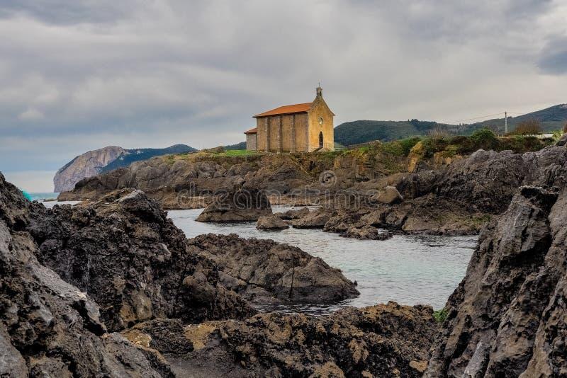 Igreja pequena de Santa Catalina na costa da vila de Mundaca em Biscaia durante um dia nebuloso foto de stock
