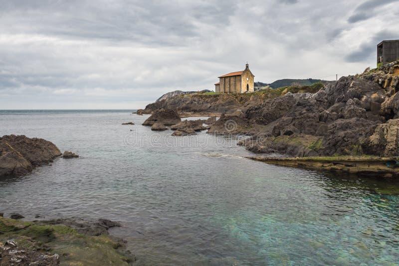 Igreja pequena de Santa Catalina na costa da vila de Mundaca em Biscaia durante um dia nebuloso fotos de stock