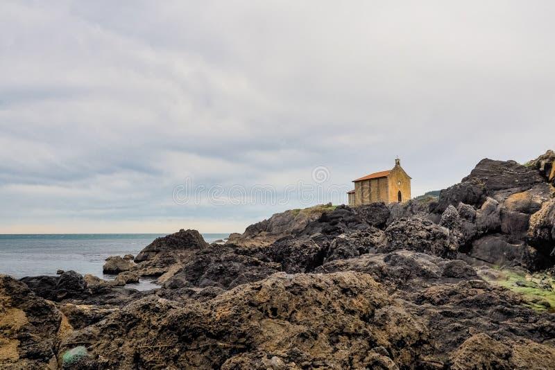 Igreja pequena de Santa Catalina na costa da vila de Mundaca em Biscaia durante um dia nebuloso fotografia de stock royalty free