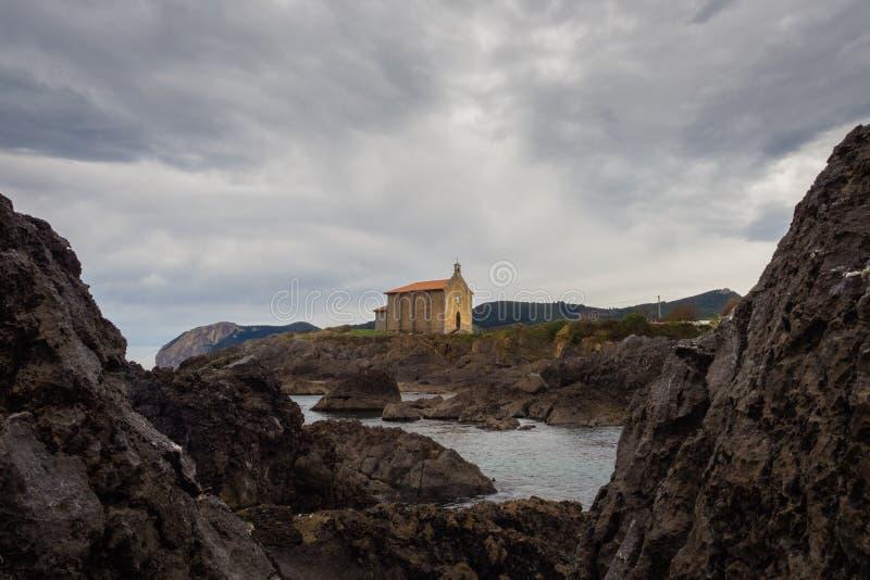 Igreja pequena de Santa Catalina na costa da vila de Mundaca em Biscaia durante um dia nebuloso fotos de stock royalty free
