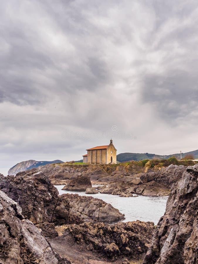 Igreja pequena de Santa Catalina na costa da vila de Mundaca em Biscaia durante um dia nebuloso imagem de stock