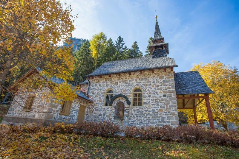 A igreja pequena no lago Braies no tempo do outono, em cumes das dolomites, no vale italianos de Pusteria, dentro do Fanes - do S fotografia de stock royalty free