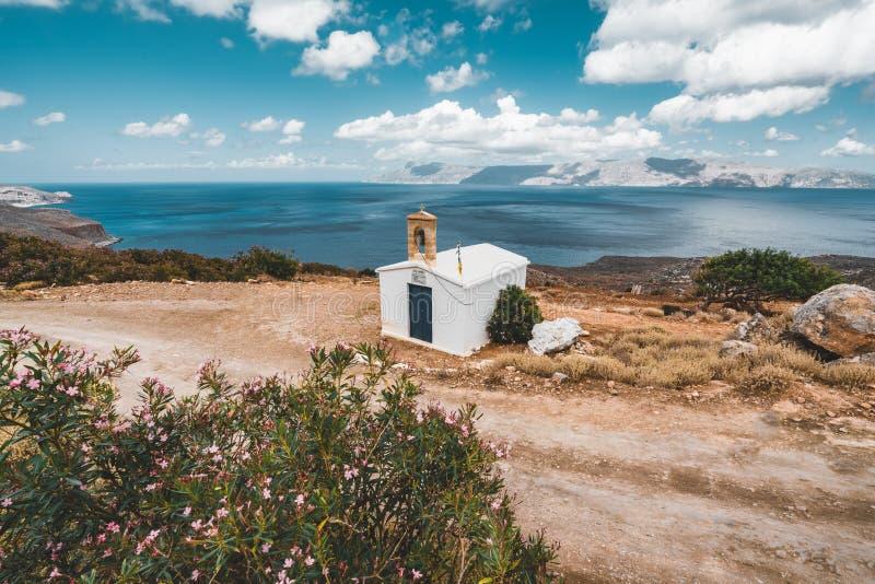 Igreja pequena pelo mar com céu azul e nuvens no fundo na ilha da Creta, Grécia fotos de stock royalty free