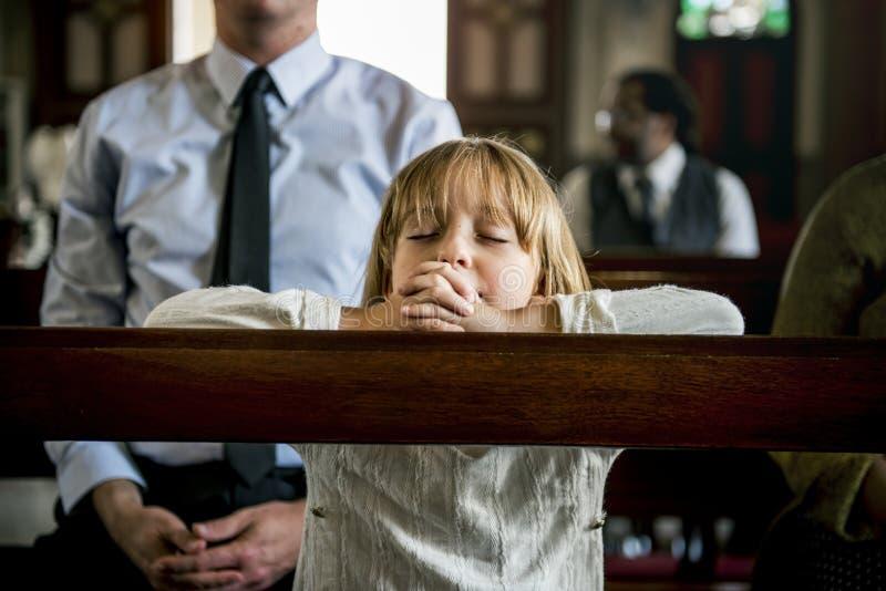 A igreja rezando da menina acredita a fé religiosa imagem de stock royalty free
