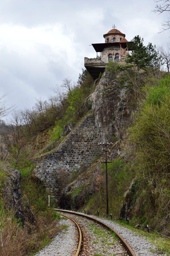 Igreja velha pequena na parede acima do túnel e da estrada de ferro imagens de stock royalty free