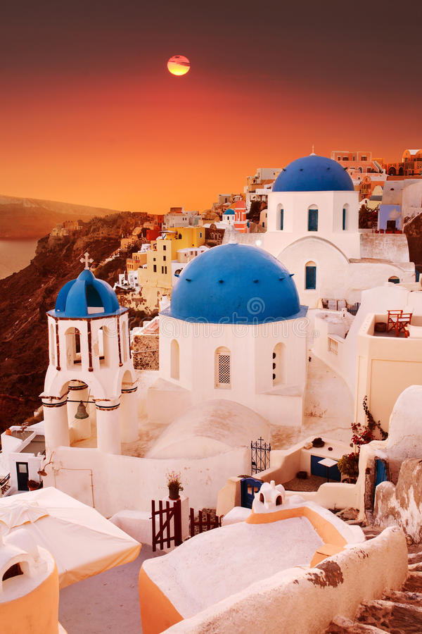Igrejas azuis da abóbada de Santorini no por do sol Vila de Oia, Greece imagens de stock royalty free