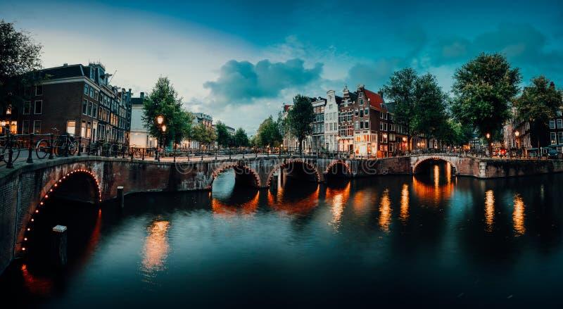 Igualación del panorama crepuscular del paisaje urbano de Amterdam con el canal, el puente y las casas medievales en la iluminaci imagen de archivo