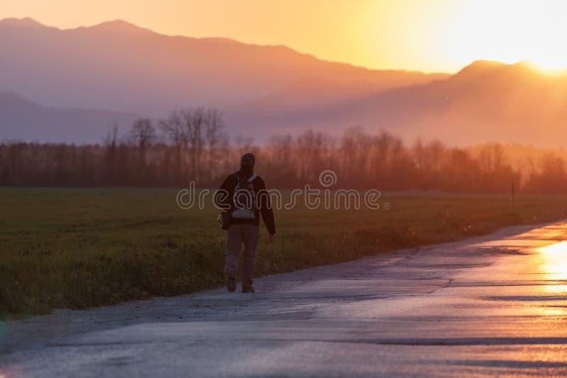 Igualando el camino que dirige al hombre de la puesta del sol que camina adelante imagen de archivo libre de regalías