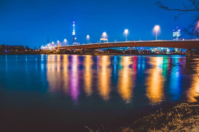 Igualando los fuegos multicolores de rascacielos modernos y el puente en Viena se reflejan en el río Visión hermosa Paisaje foto de archivo libre de regalías