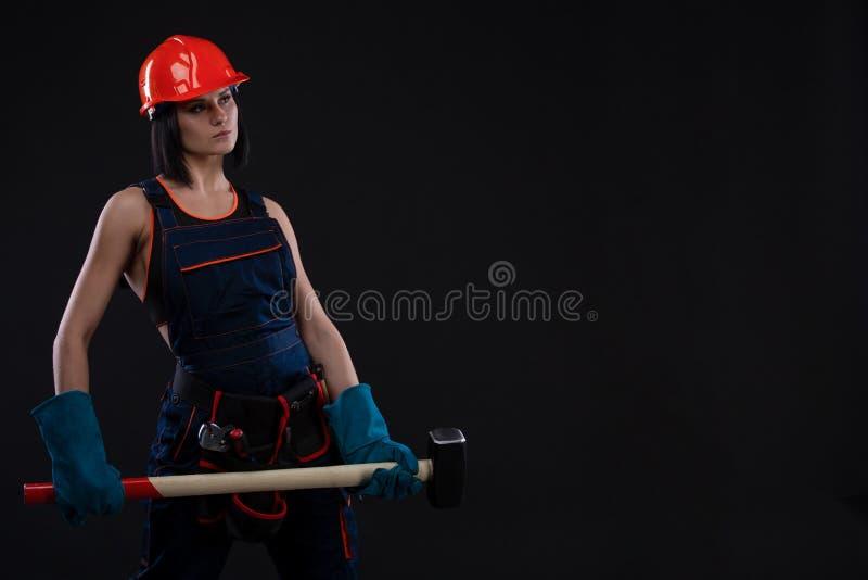 Igualdad y feminismo del sexo Muchacha atractiva en el casco de seguridad que sostiene la herramienta del martillo Funcionamiento fotos de archivo libres de regalías