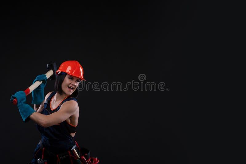 Igualdad y feminismo del sexo Muchacha atractiva en el casco de seguridad que sostiene la herramienta del martillo Funcionamiento imagen de archivo libre de regalías