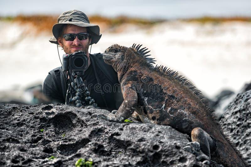Iguana de las Islas Galápagos y fotógrafo turístico de la fauna de la naturaleza que toman la imagen imagenes de archivo