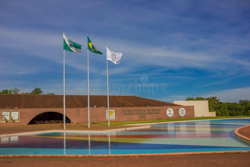 IGUAZU BRASILIEN - MAJ 14, 2016: den brasilianska flaggan bredvid tillståndet och staden sjunker på ingången av iguazuen arkivbild