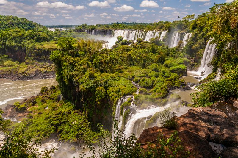 Iguazu rainfalls with green vegetation and some clouds in the sky royalty free stock image