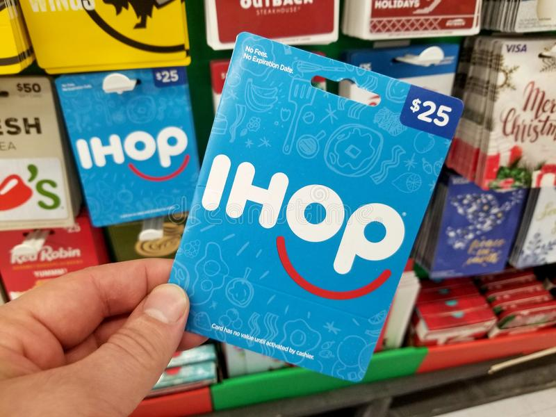 IHOP gift card in a hand. PLATTSBURGH, USA - JANUARY 21, 2019 : IHOP pancake house gift card in a hand over a shelves with different giftcards in a Walmart store royalty free stock images