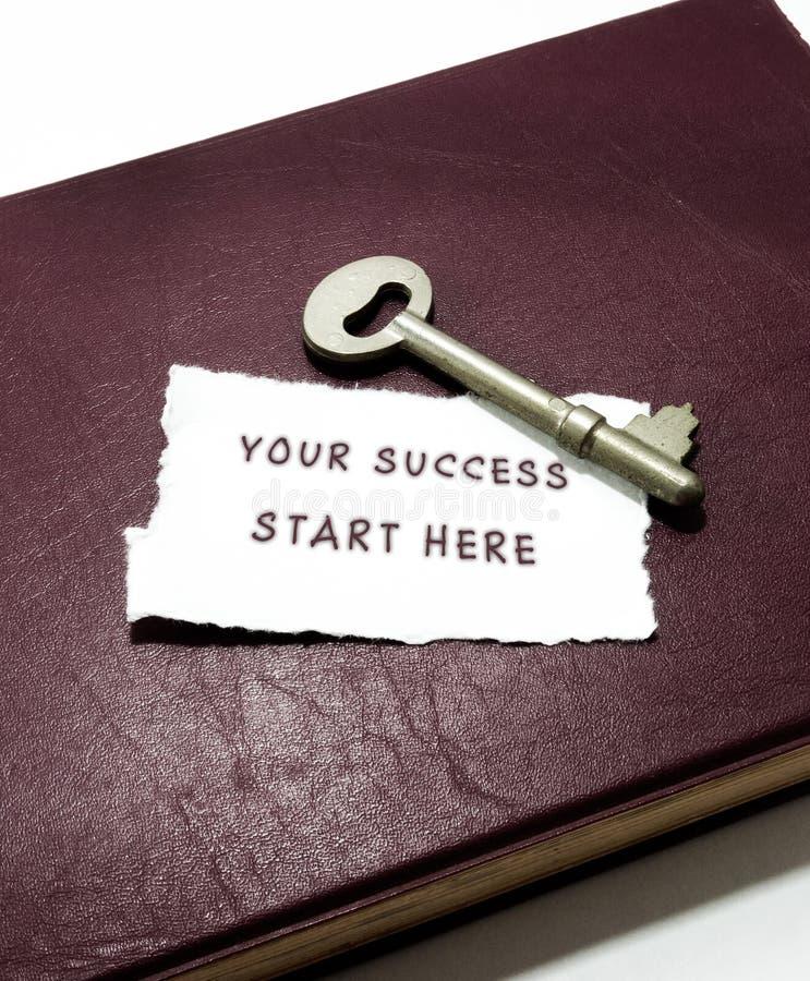 Ihr Erfolgsanfang hier mit Schlüssel auf Buch stockfoto