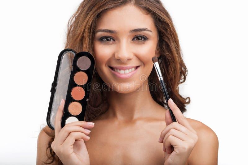 Ihr Make-upmaterial zeigen. Schöne junge Frauen, die den mak halten stockfotografie