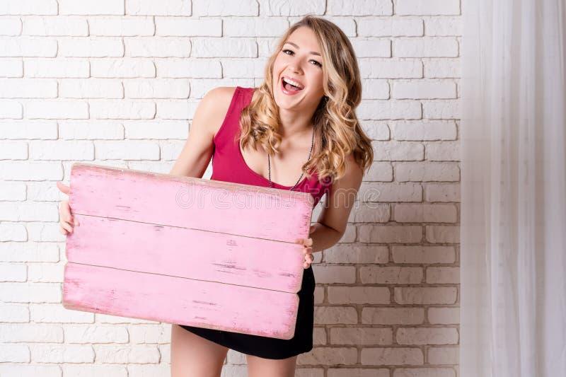 Ihr Text hier Hübsche junge lächelnde Blondine, die leeres leeres Brett halten Studioporträt mit weißer Backsteinmauer an lizenzfreie stockfotos