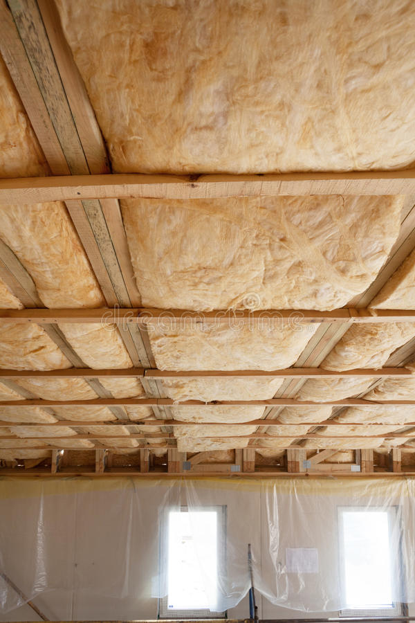 Iinsulation of attic with fiberglass cold barrier and insulation material. Iinsulation of attic with fiberglass cold barrier and insulation material stock photos
