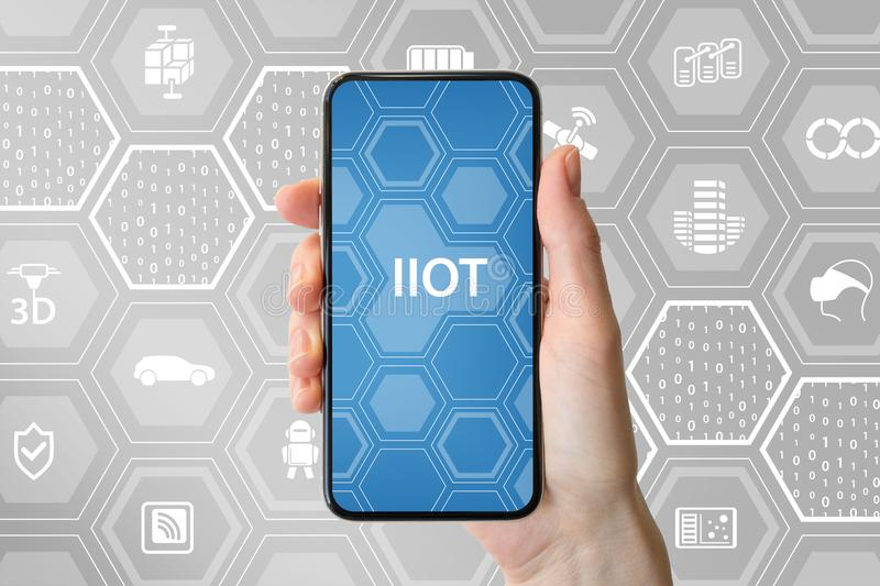IIOT industrial internet of things text displayed on screen of modern frameless smartphone. Hand holding smartphone.  royalty free stock photo