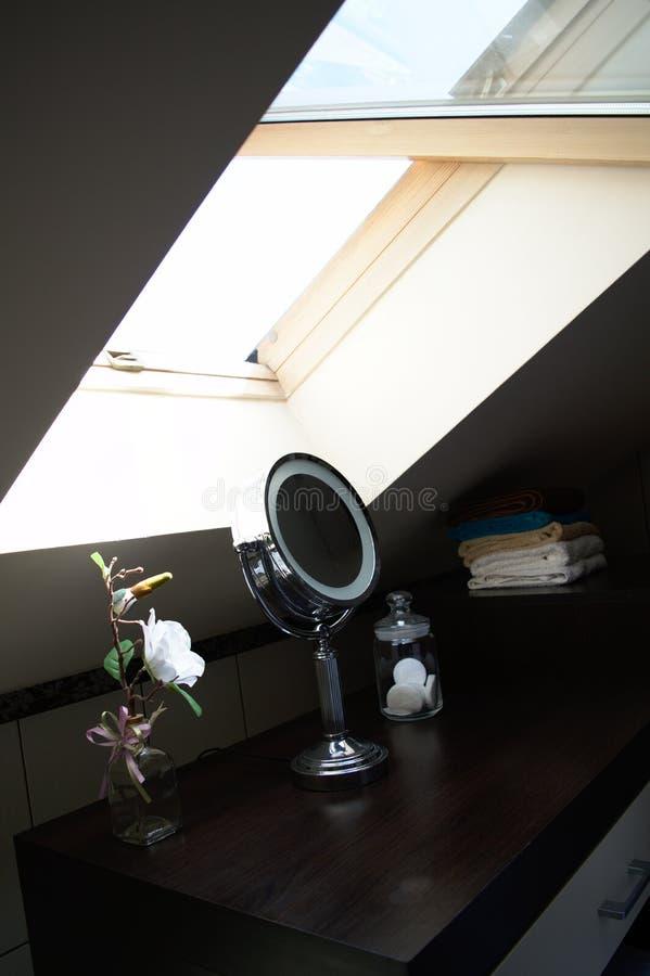 Ijdelheidslijst met ronde spiegel onder een dakraam stock foto